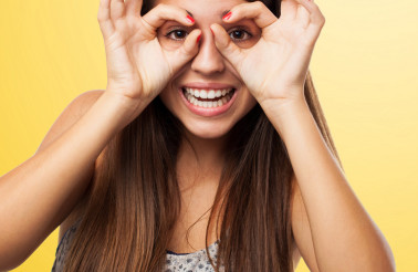 portrait of young woman doing a glasses gesture closeup