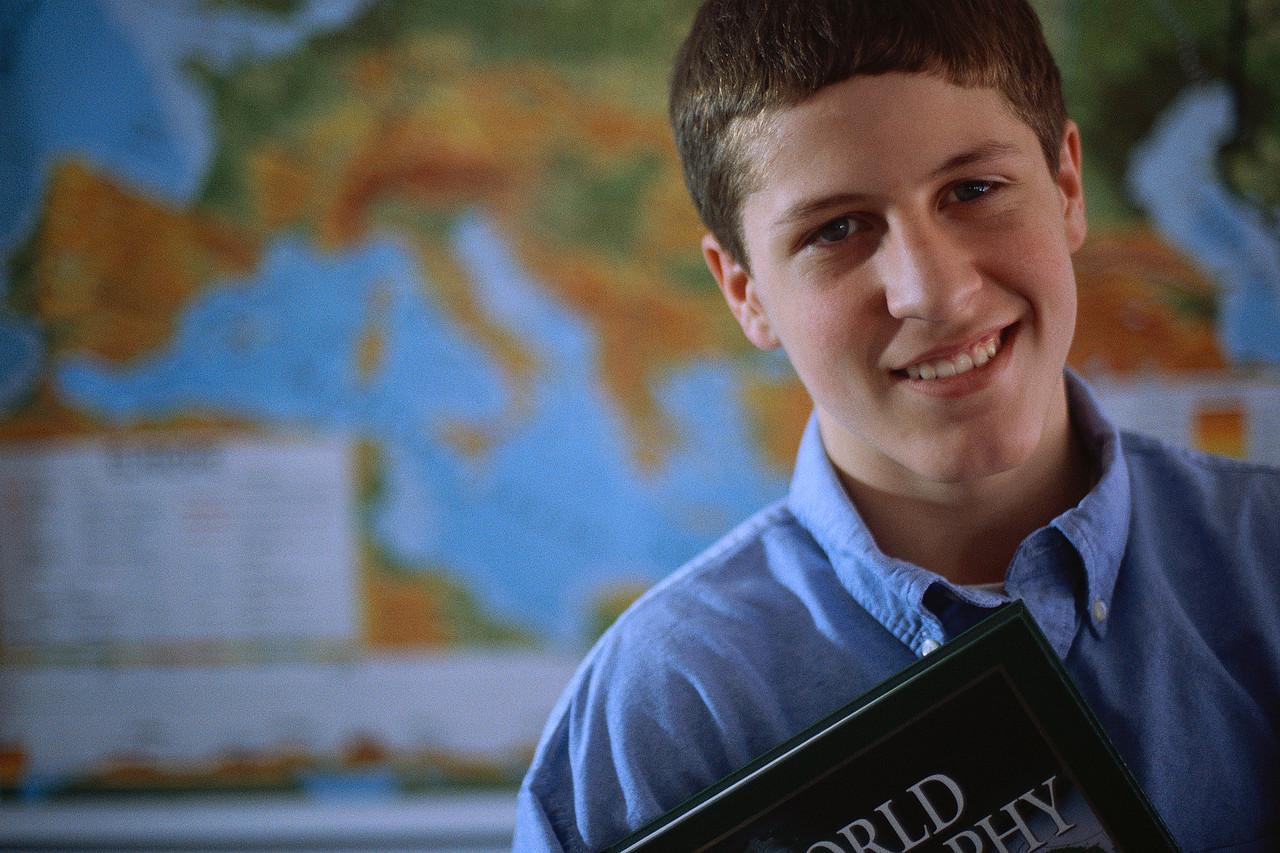 Adolescent Boy Holding a Textbook ca. 2000