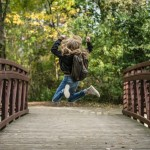 girl-jumping-on-the-bridge-wearing-black-jacket-214573