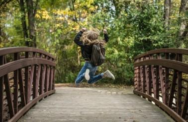 girl-jumping-on-the-bridge-wearing-black-jacket-214573